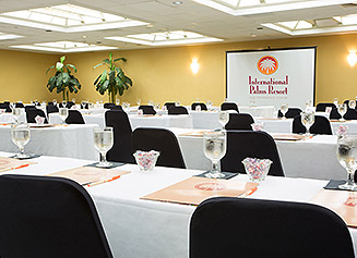 Meeting room setup classroom style with white tablecloths and black chairs