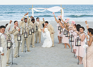 Bride and Groom kissing on the beach with groomsmen and bridesmaids on each side of them